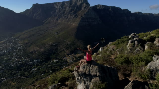 aerial view of woman celebrating achievement on mountain top - lion's head mountain stock videos and b-roll footage