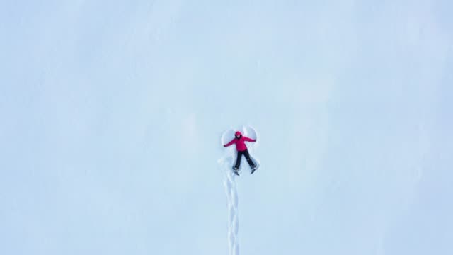 aerial view of woman doing a snow angel - canada video stock e b–roll