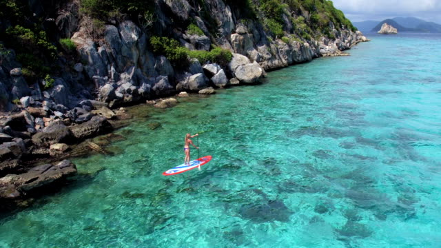 aerial view of woman exploring the Caribbean on paddleboard