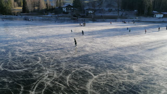 aerial view of woman iceskating on frozen lake - ice skating stock videos & royalty-free footage