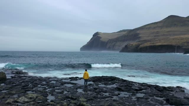 Vista aérea da mulher no capa amarelo que olha a vista cénico do beira-mar em consoles de Faroe
