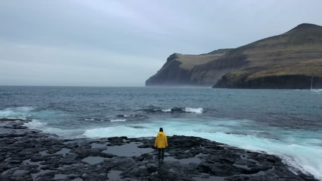 aerial view of woman in yellow raincoat  looking at scenic  view of seaside in faroe islands - raincoat stock videos & royalty-free footage