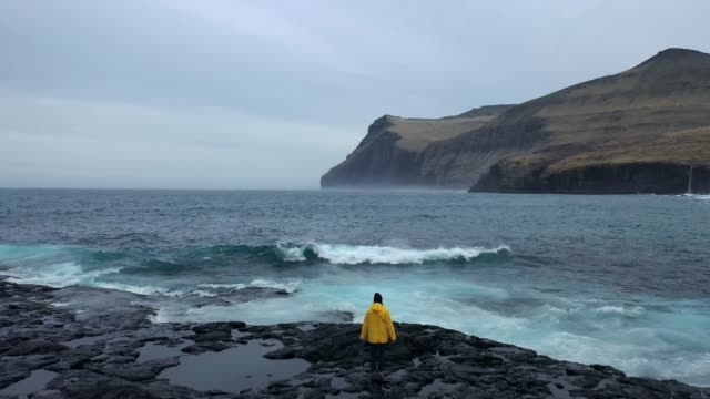 aerial view of woman in yellow raincoat  looking at scenic  view of seaside in faroe islands - rear view stock videos & royalty-free footage