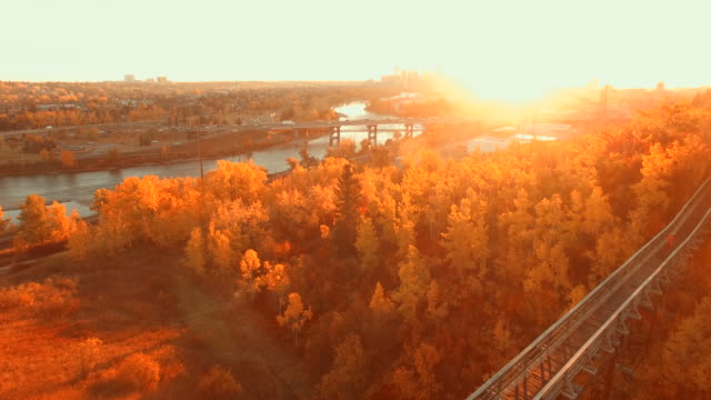 Aerial view of woman jogging across wooden bridge at sunset, city in the distance