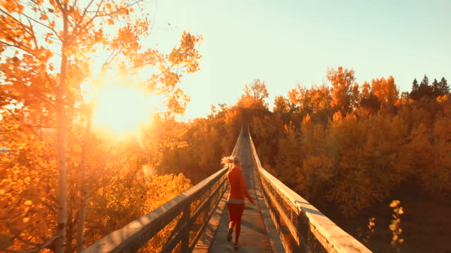 Aerial view of woman jogging across wooden bridge at sunset while using smartphone