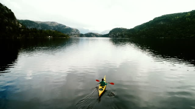 aerial view of woman kayaking on the lake in mountains - kayak video stock e b–roll