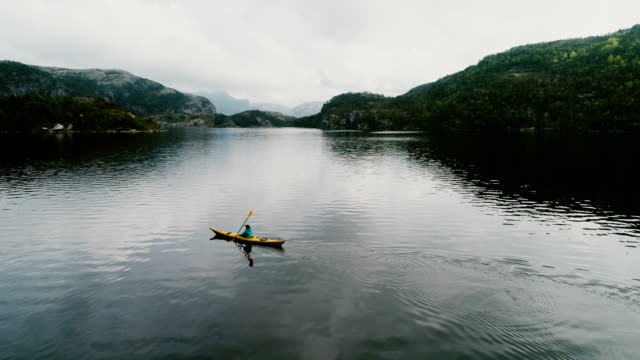 aerial view of woman kayaking on the lake in mountains - tranquility stock videos & royalty-free footage