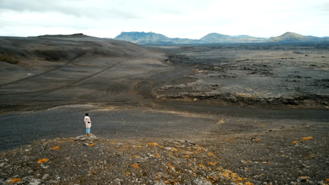 aerial view of woman looking  at barren  in iceland - barren stock videos & royalty-free footage