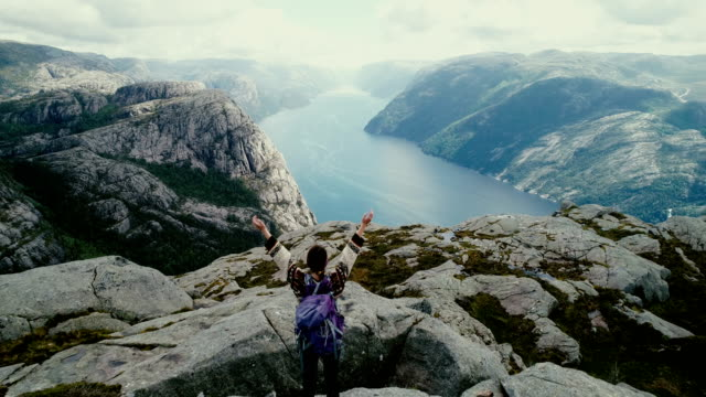 aerial view of woman looking at lysefjorden from preikestolen - arms raised stock videos & royalty-free footage