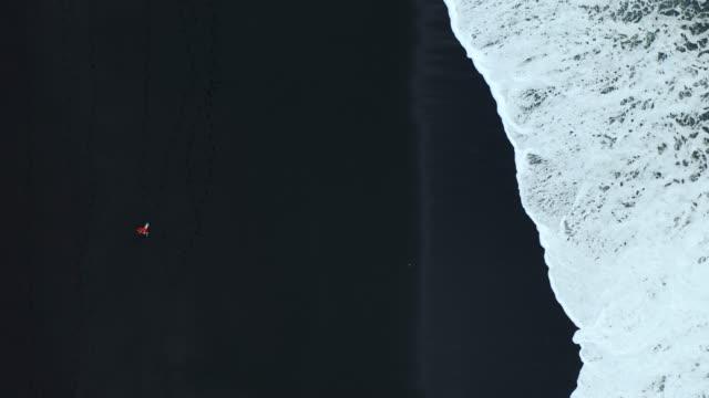 vídeos y material grabado en eventos de stock de vista aérea de la mujer en la playa de arena negra en islandia - imagen minimalista