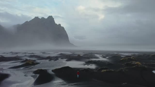 aerial view of woman on black sand beach in iceland - dramatic landscape stock videos & royalty-free footage