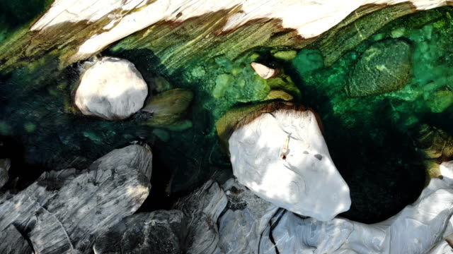 aerial view of woman  on rock near the river in lavertezzo - ticino canton stock videos and b-roll footage