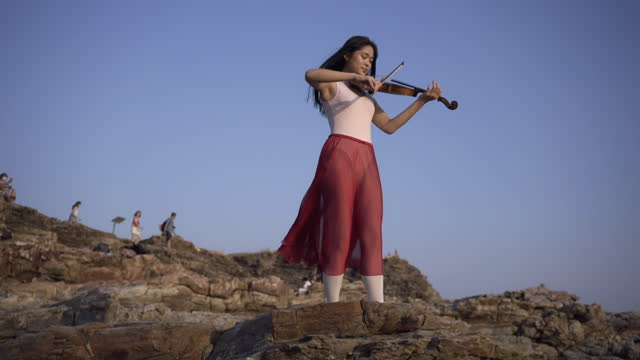 aerial view of woman on the mountain playing the violin on sea background at sunset . - violinist stock videos & royalty-free footage