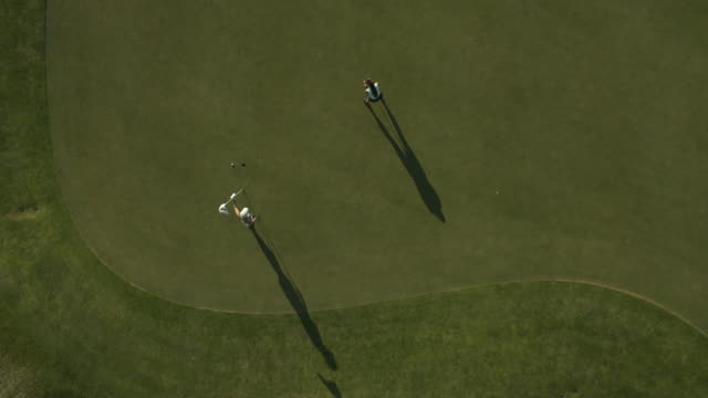 vídeos y material grabado en eventos de stock de aerial view of woman playing golf on green / cedar hills, utah, united states - putt