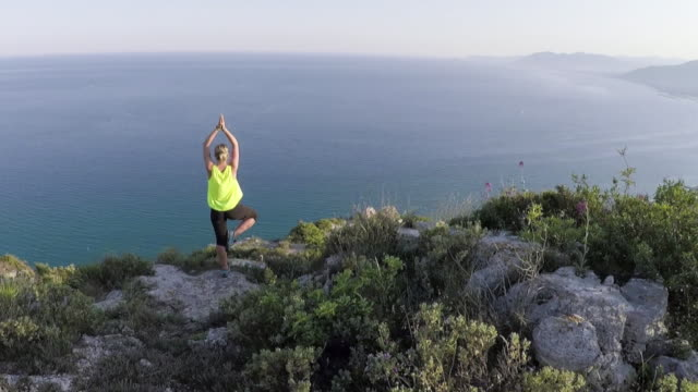 Aerial view of woman practicing yoga moves, above sea