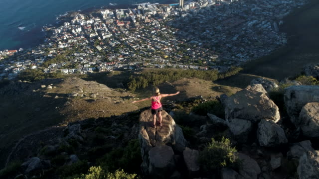 aerial view of woman reaching mountain top - lion's head mountain stock videos and b-roll footage