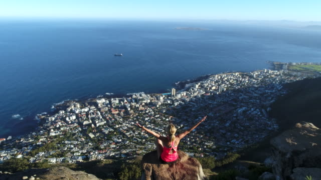 aerial view of woman reaching mountain top - south africa stock videos & royalty-free footage