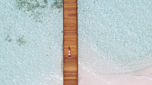 Aerial view of woman relaxing on a wooden pier, Maldives