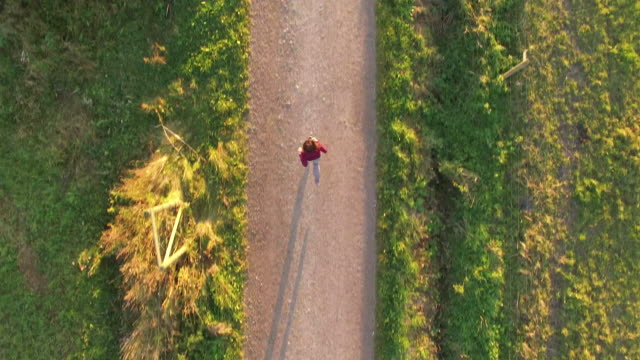 Aerial view of woman running on a dirt road at sunset, Finland.