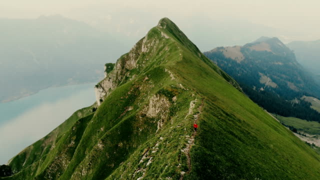 Aerial view of woman running on the mountain ridge in Swiss Alps