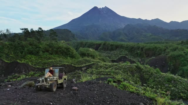 aerial view of woman sitting on  old fashioned suv on the background of merapi volcano - java stock videos & royalty-free footage