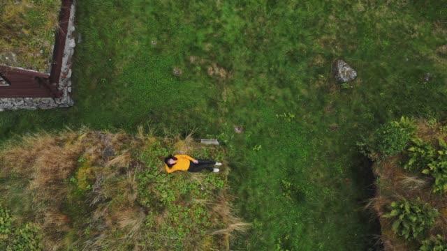 vídeos y material grabado en eventos de stock de vista aérea de la mujer sentada en el techo de la cabaña en musgo en el fondo del fiordo - acostado