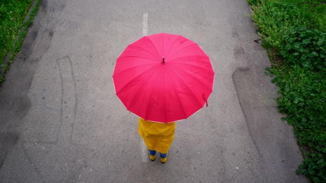 vídeos de stock, filmes e b-roll de vista aérea do guarda-chuva giratório da mulher - chapéu