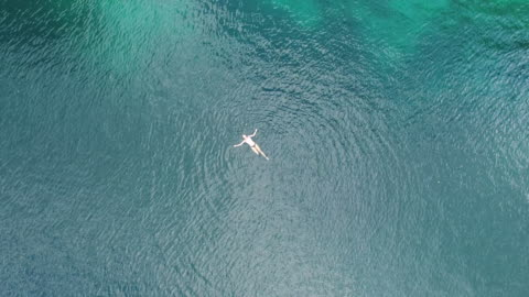 aerial (drone) view of woman swimming and karst topography - floating on water stock videos & royalty-free footage