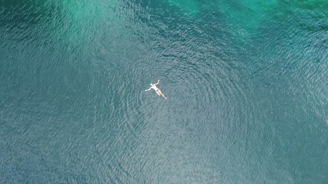 aerial (drone) view of woman swimming and karst topography - galleggiare sull'acqua video stock e b–roll