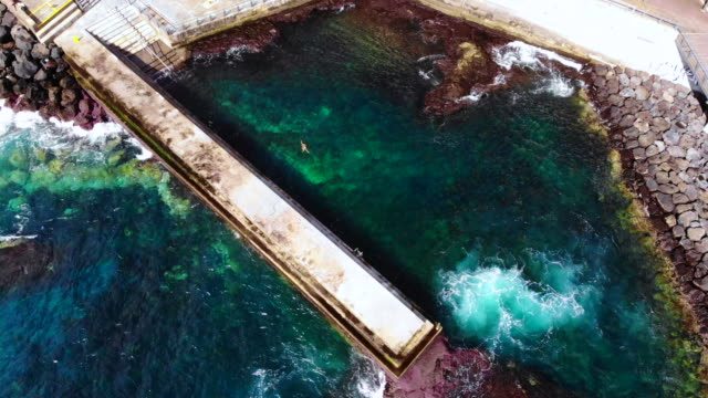 aerial view of woman swimming in artificial beach with pier and concrete in the azores islands. - atlantikinseln stock-videos und b-roll-filmmaterial