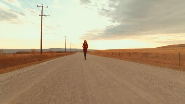 Aerial view of woman walking along dirt road at sunset