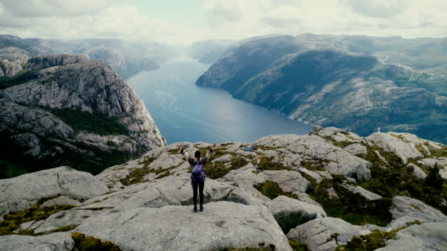 aerial view of woman walking and  looking at lysefjorden from preikestolen - mountain stock videos & royalty-free footage