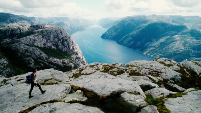 aerial view of woman walking and  looking at lysefjorden from preikestolen - rucksack stock videos and b-roll footage