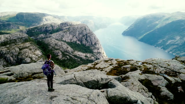aerial view of woman walking and  looking at lysefjorden from preikestolen - norway stock videos & royalty-free footage