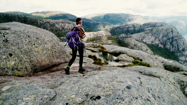 Aerial view of woman walking and  looking at Lysefjorden from Preikestolen