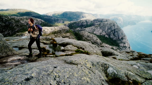 aerial view of woman walking and  looking at lysefjorden from preikestolen - north stock videos and b-roll footage