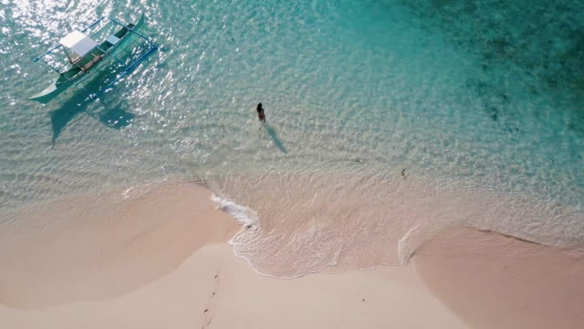 Aerial (drone) view of woman walking into ocean