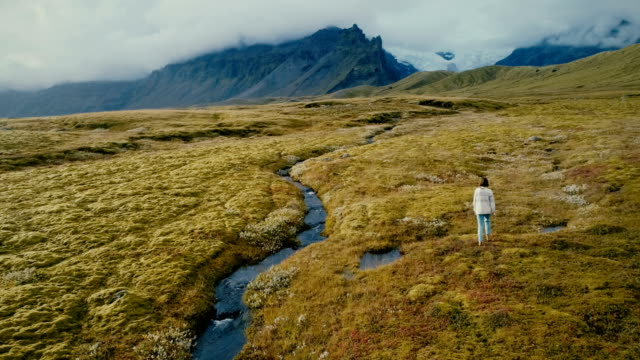 aerial view of woman walking near the river with view on the glacier - eco tourism stock videos & royalty-free footage