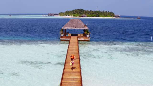 Aerial view of woman walking on a wooden pier, Maldives