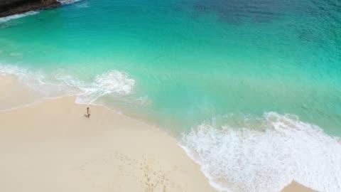 stockvideo's en b-roll-footage met luchtfoto van de vrouw lopen op scenic beach op nusa penida - bali
