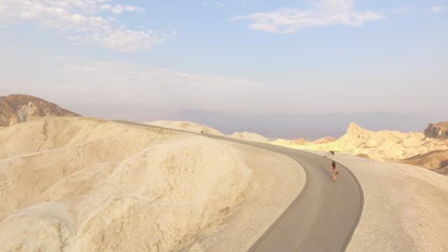 vídeos y material grabado en eventos de stock de aerial view of woman walking up empty road in desert - doblado actividad física