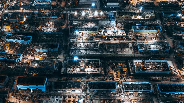 t/l pan aerial view of working construction site at night - building activity stock videos & royalty-free footage