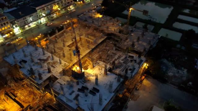 luftbild von der baustelle in stadt nachts arbeiten - baustelle stock-videos und b-roll-filmmaterial