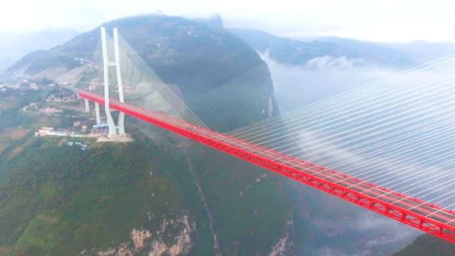 stockvideo's en b-roll-footage met luchtfoto van's werelds hoogste hangbrug, beipanjiang, ghuizhou, china - brug mens gemaakte bouwwerken