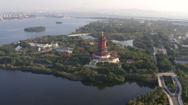 vídeos de stock, filmes e b-roll de aerial view of xiamen yuanbo garden, with lake foreground and chinese traditional pagoda tower - ponto turístico local