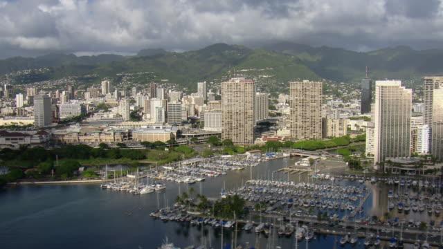 vídeos y material grabado en eventos de stock de aerial view of yachts docked in honolulu, hawaii surrounded by coastal skyscrapers. - honolulu