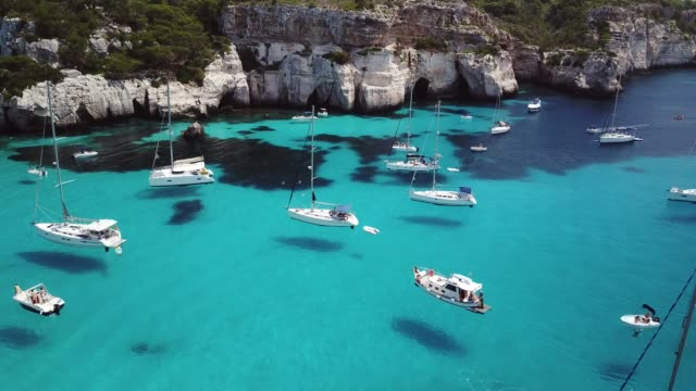 vídeos de stock e filmes b-roll de aerial view of yachts moored in the mediterranean, menorca, spain - azul turquesa