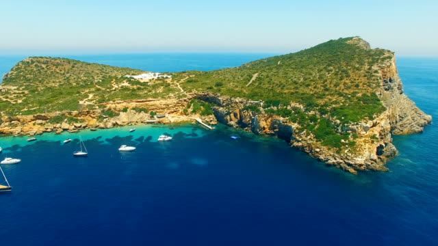 aerial view of yatch in amazing, unspoiled and idyllic beach on a little island - balearic islands stock videos and b-roll footage