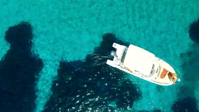 aerial view of yatch in amazing, unspoiled and idyllic beach - silvestre stock-videos und b-roll-filmmaterial