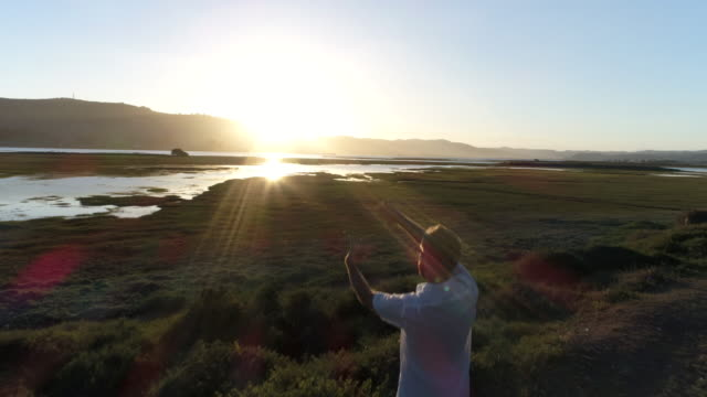 Aerial view of young man framing sunset